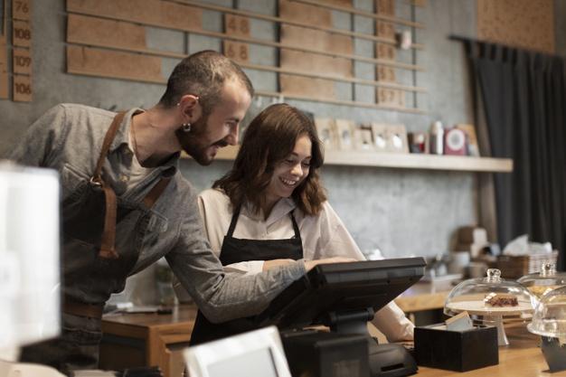 Vemos dois balconistas de uma loja enquanto aprendem a operar o caixa touchscreen (imagem ilustrativa).