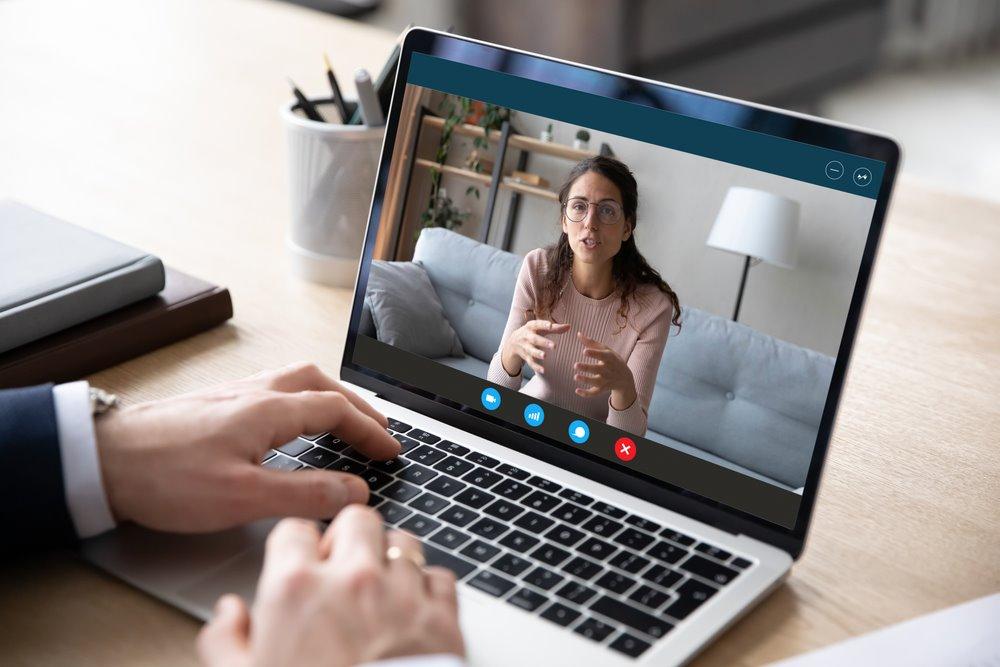 Vemos duas pessoas conversando por vídeoconferência (imagem ilustrativa). Texto: comprar franquia.