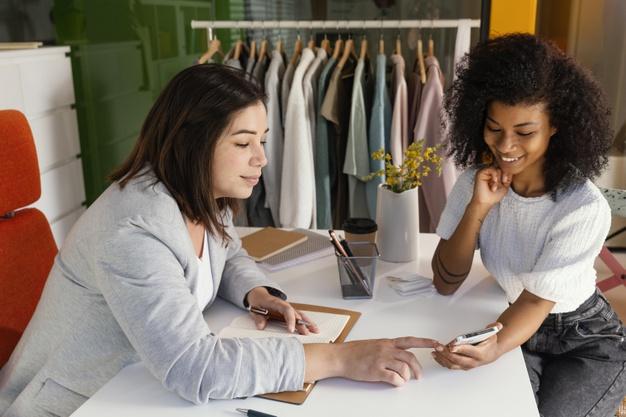 Vemos uma vendedora e uma cliente em uma loja de roupas (imagem ilustrativa).