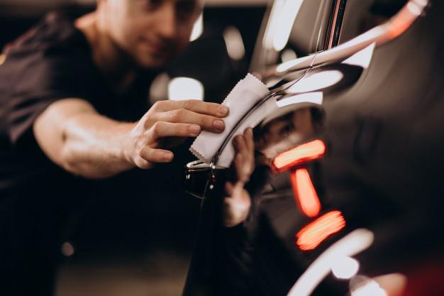 Vemos um homem fazendo o polimento da pintura de um carro (imagem ilustrativa). Texto: abrir um lava jato.