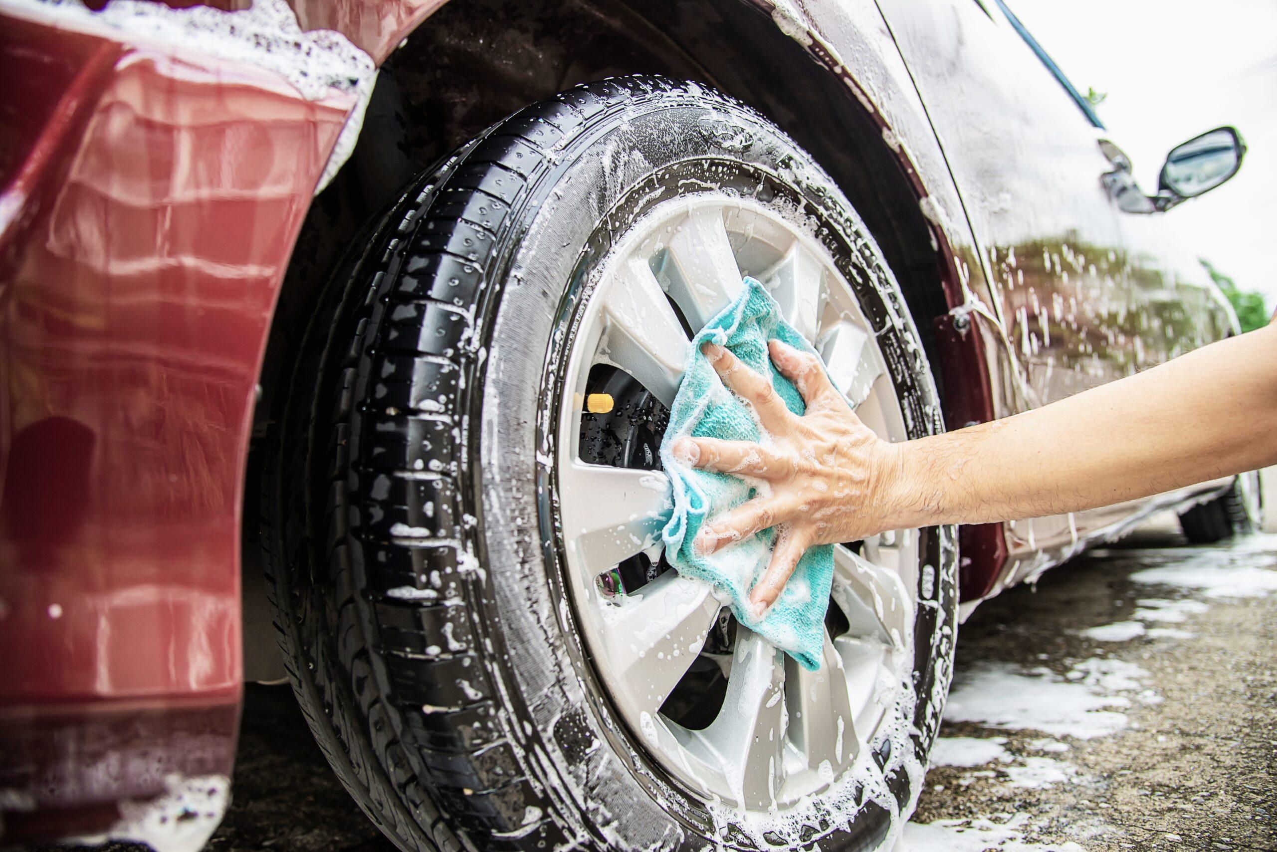 Vemo uma pessoa lavando a roda de um carro com água e sabão (imagem ilustrativa).