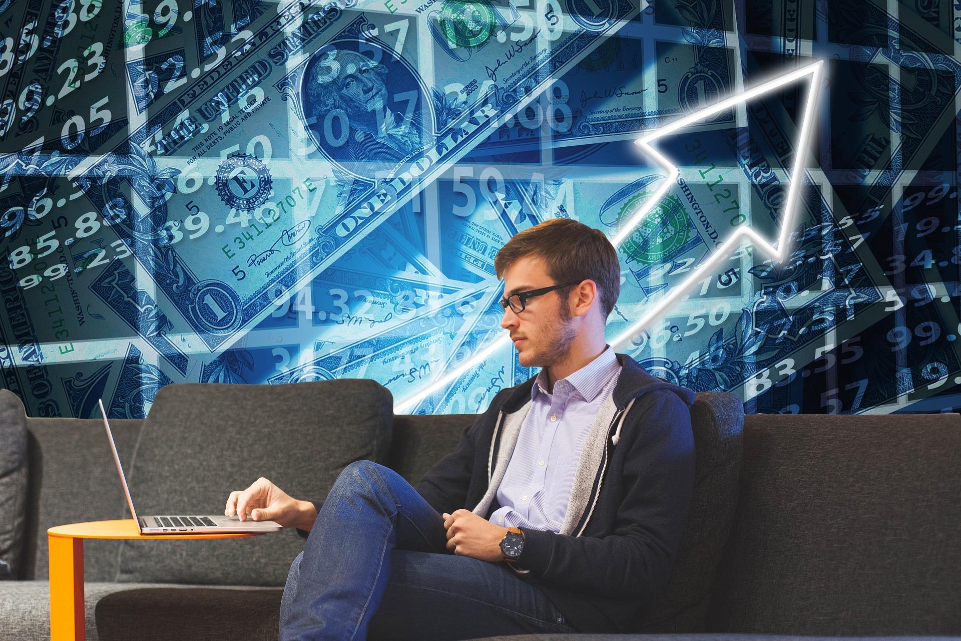 Vemos um home olhando para um computador com imagens de gráficos e dinheiro atrás dele (imagem ilustrativa). Texto: abrir negócio de forma descomplicada.
