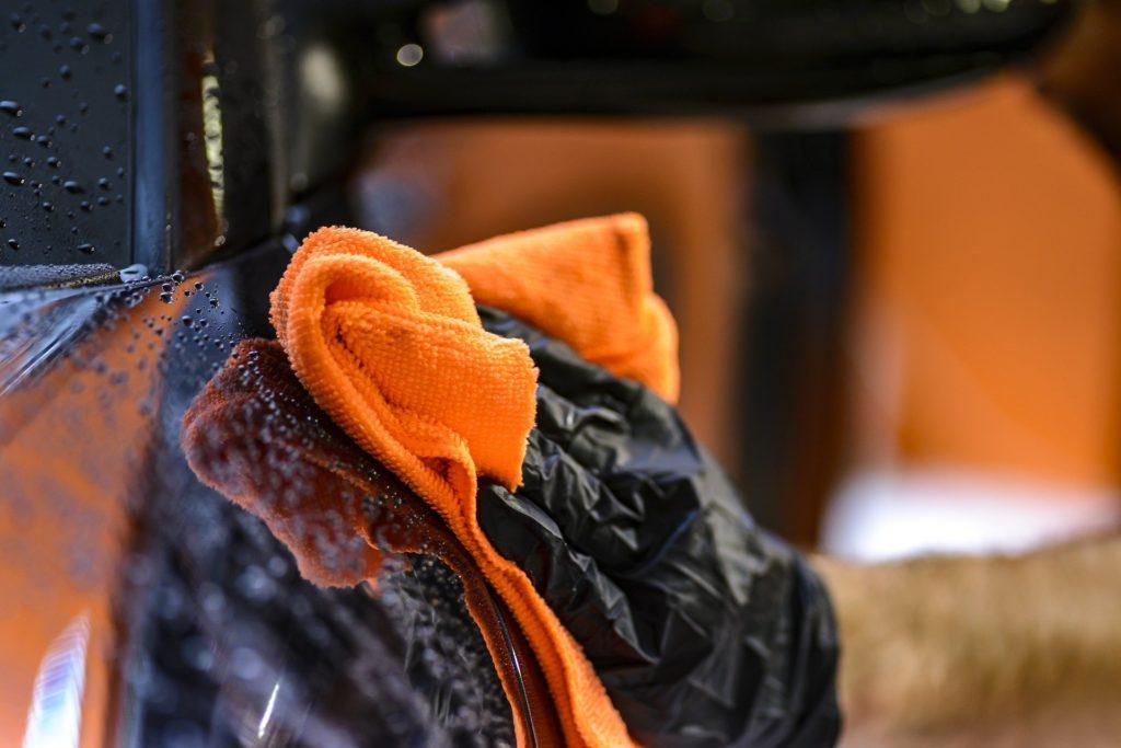 Vemos que uma pessoa está realizando a limpeza da parte externa de um veículo com uma flanela na cor laranja (imagem ilustrativa). Texto: como montar um lava jato.