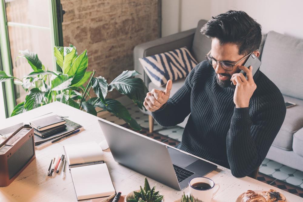 Vemos um homem falar ao telefone em seu escritório, em casa (imagem ilustrativa). Texto: como montar um lava jato.
