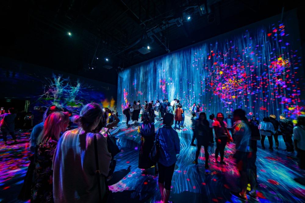 Vemos algumas pessoas se divertindo em um espaço com muitas luzes, aparentando ser uma festa (imagem ilustrativa). Texto: franquia de entretenimento.