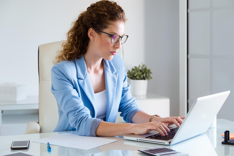 Vemos uma mulher trabalhando em seu escritório (imagem ilustrativa). Texto: franquias até 100 mil.