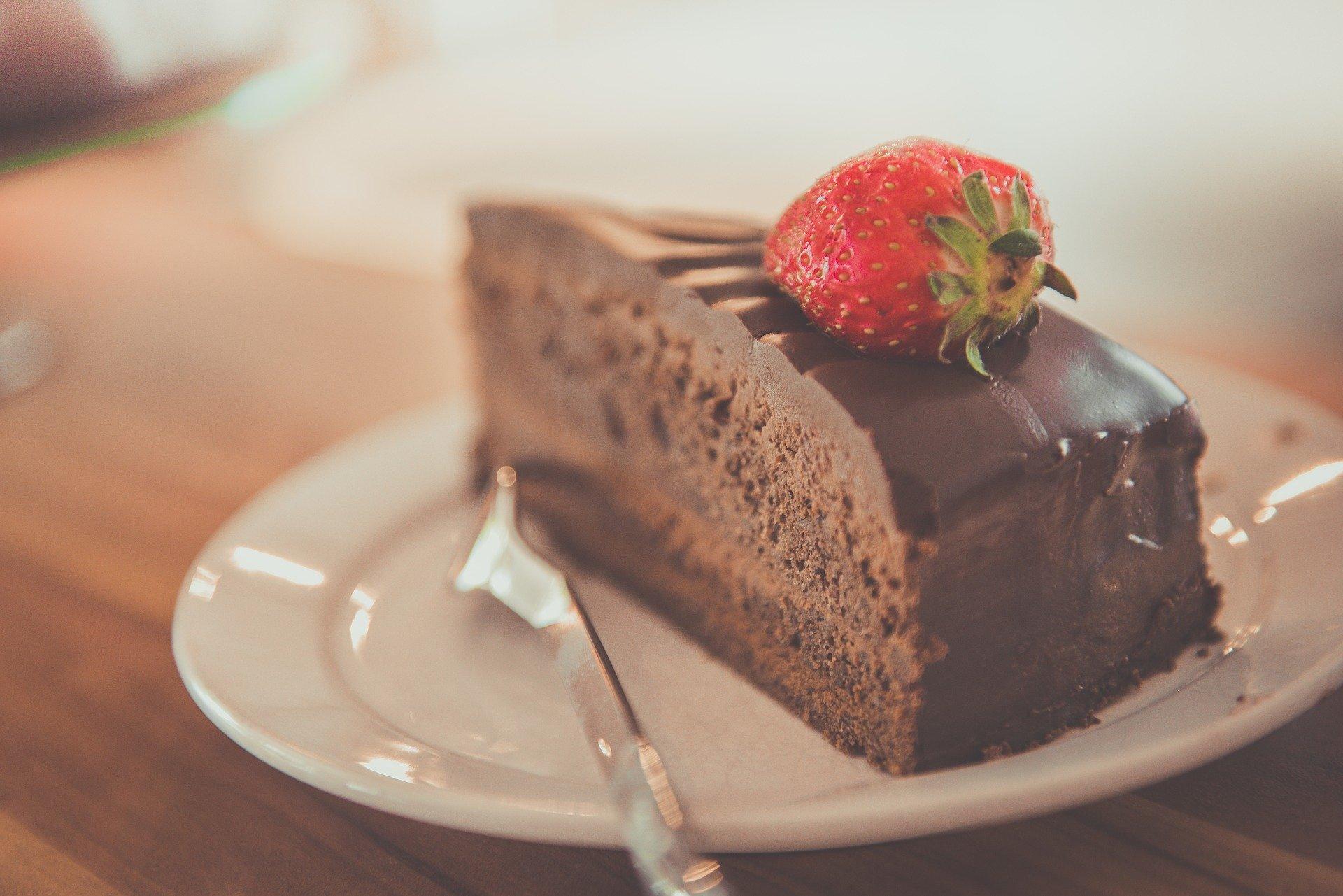Vemos um pedaço de bolo de chocolate (imagem ilustrativa). Texto: franquias até 100 mil.