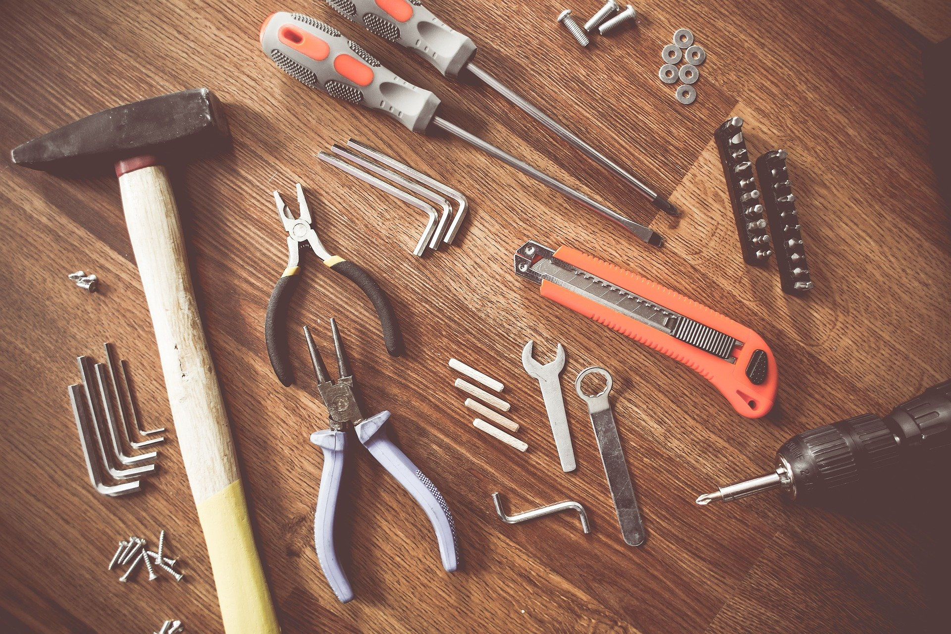Vemos, sobre uma superfície de madeira, diversas ferramentas, como martelo, estilete, alicate etc. (imagem ilustrativa).