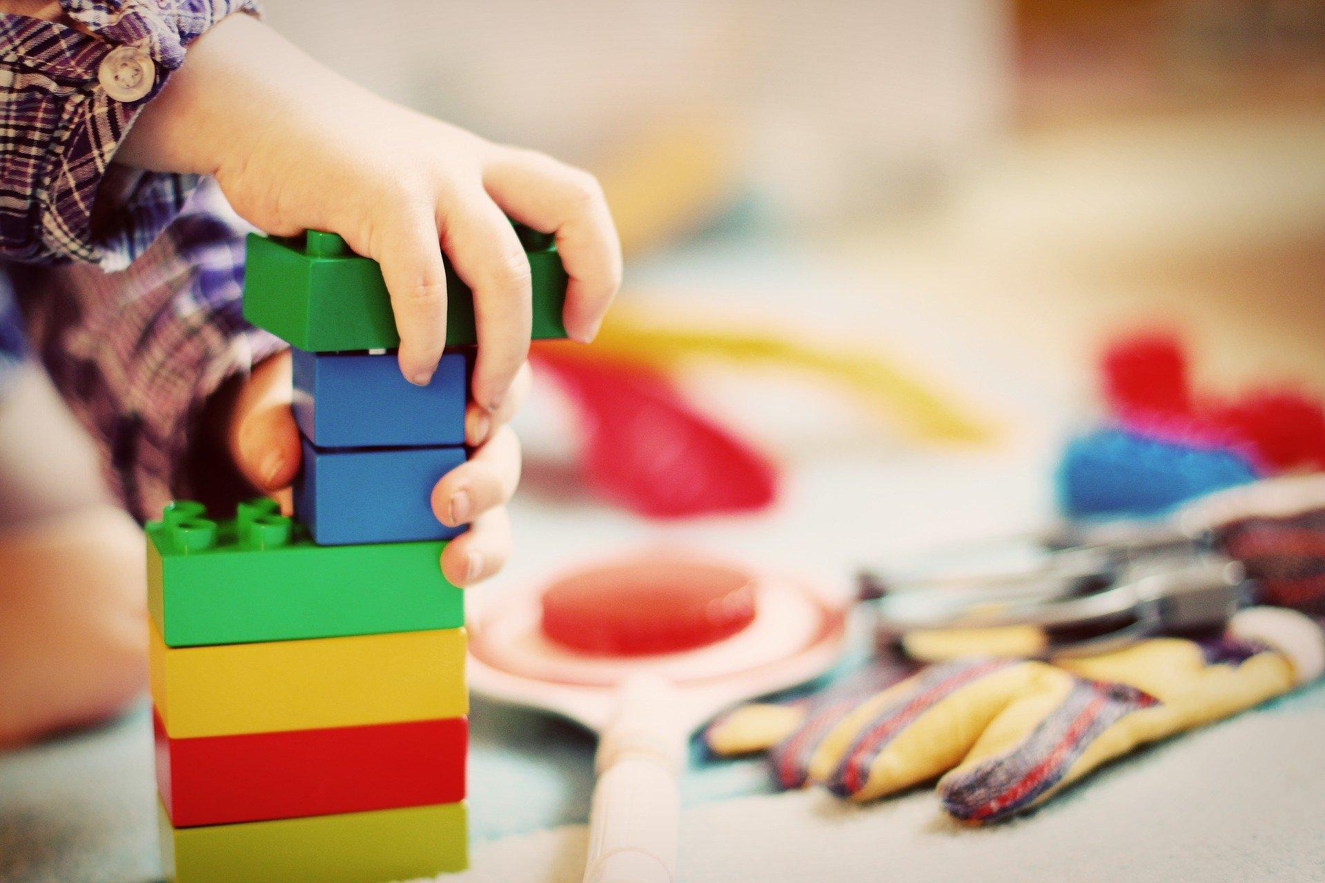 Vemos uma criança brincar com algumas peças de encaixe (imagem ilustrativa). Texto: franquias até 100 mil.