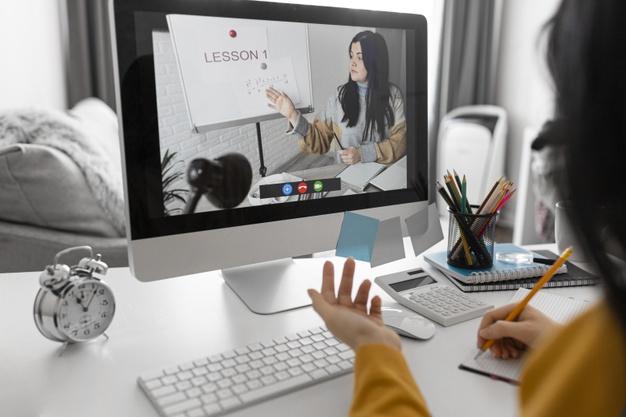Vemos uma mulher tendo aula on-line na frente do computador (imagem ilustrativa).