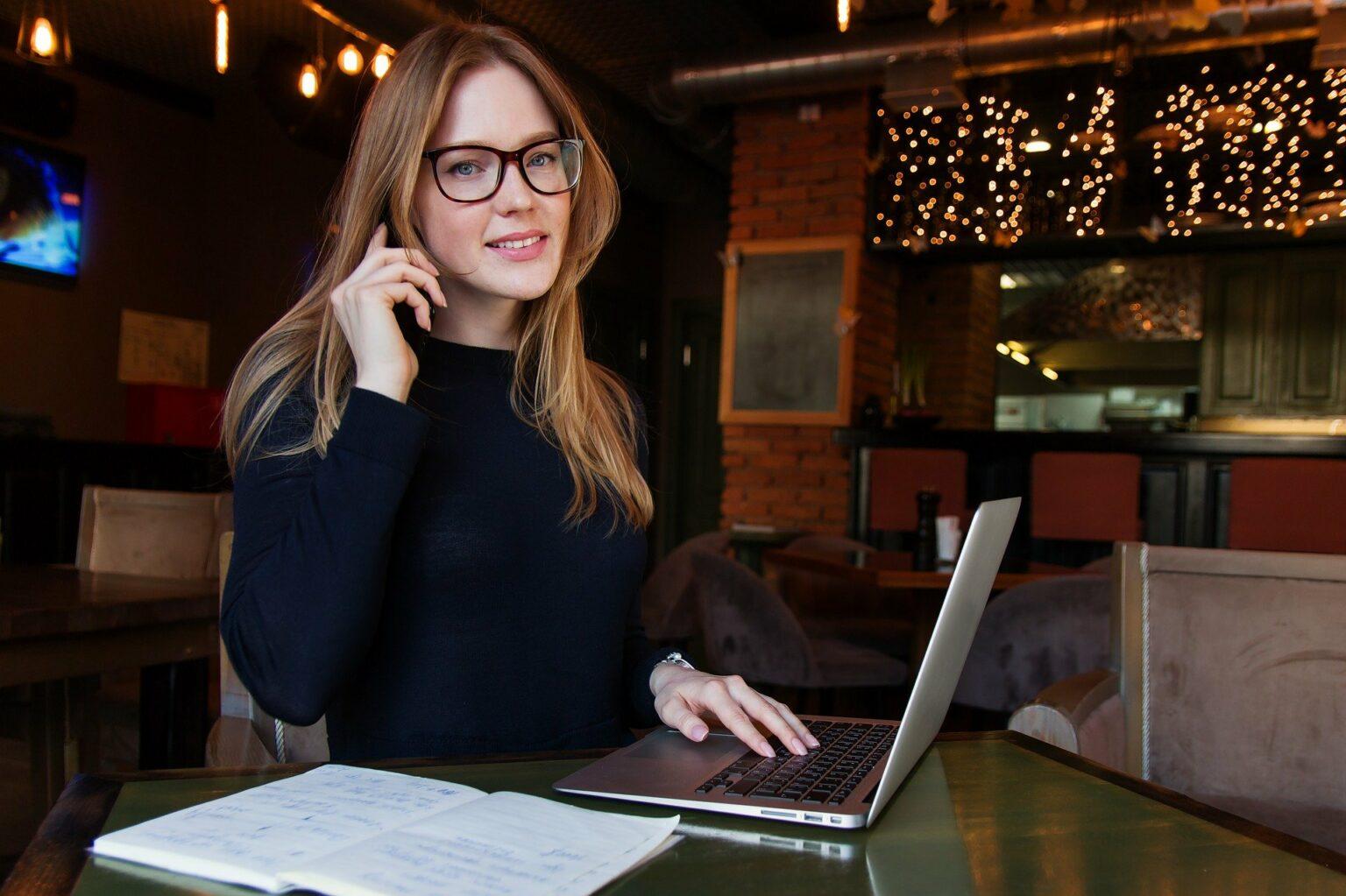 Mulher sentada em uma mesa em frente um computador.