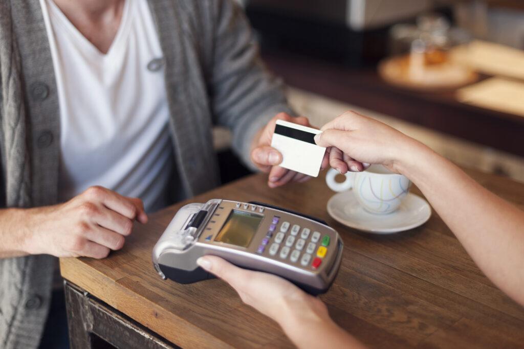 Imagem de um cliente passando o cartão em uma máquina de pagamento (imagem ilustrativa). Texto: franquias até 5 mil.
