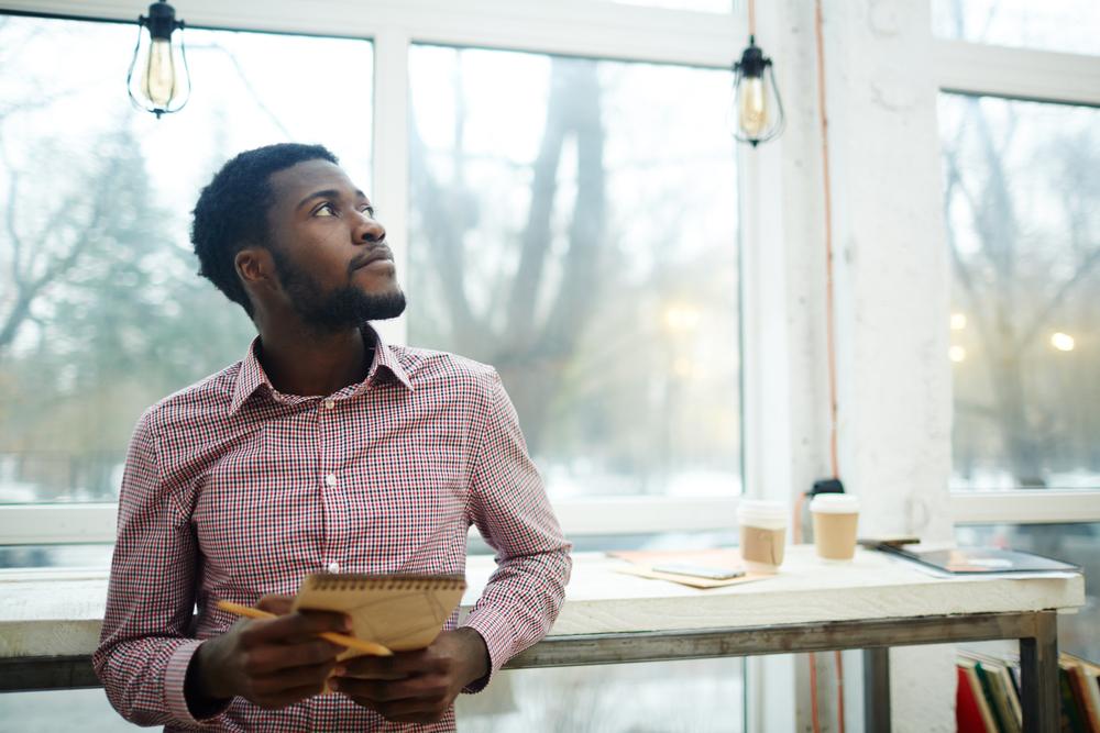 Vemos um homem negro, muito bem vestido, com expressão pensativa refletindo sobre uma franquia ideal para cidade pequena à frente de uma mesa com um bloco de papel e lápis na mão (imagem ilustrativa).
