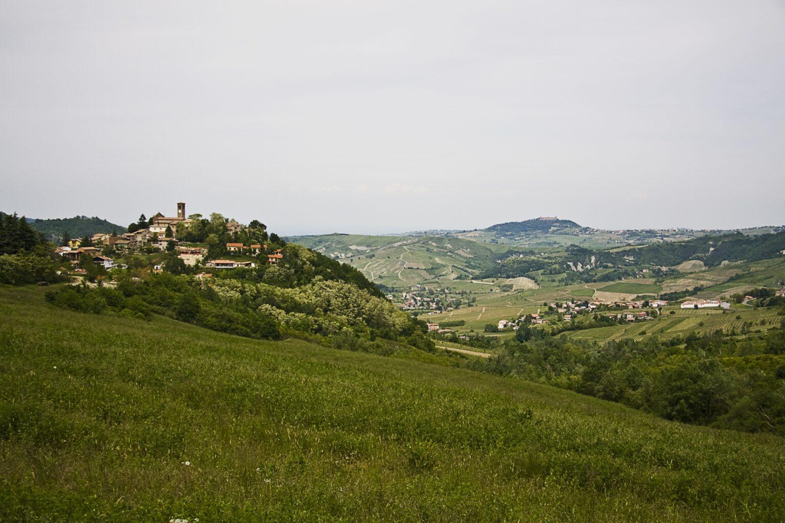 Vemos uma grande área verde. Ao longe, um mirante com algumas casa. Mais ao fundo, é possível começar a visualizar os limites de uma pequena cidade.