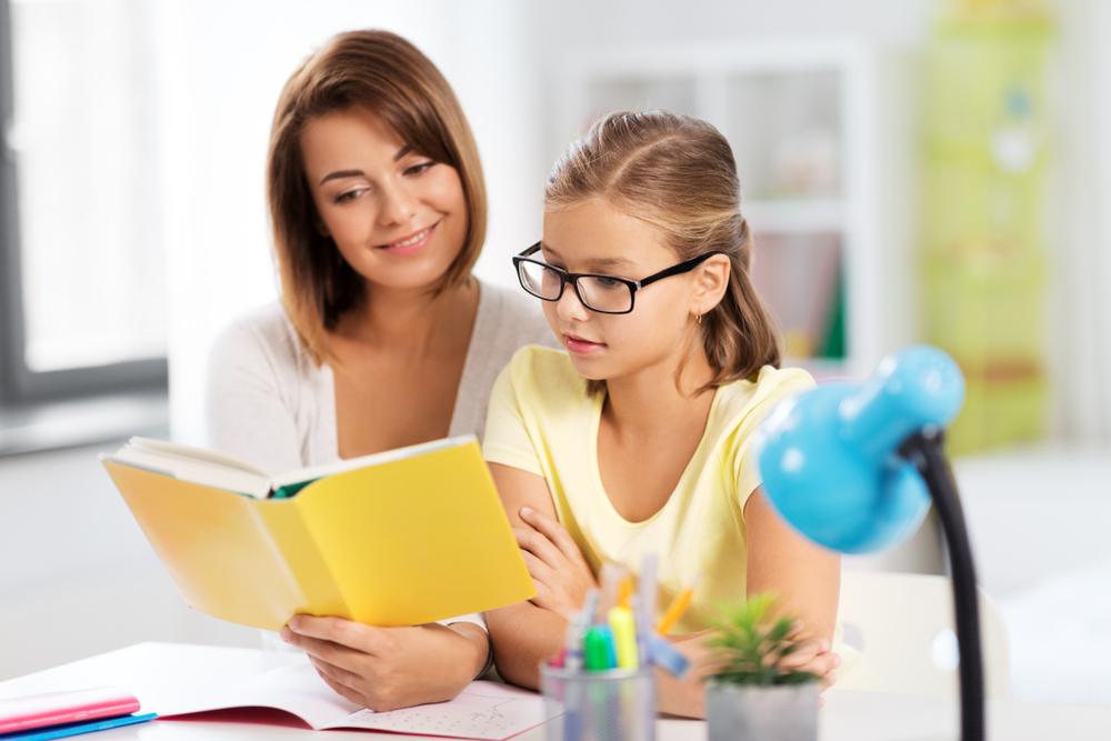 Vemos professora e aluna lendo um livro em um ambiente escolar que pode ser em uma franquia ideal para cidade pequena.