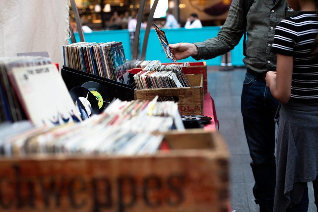 Vemos algumas pessoas no que parece ser uma venda de discos antigos em uma cidade turística (imagem ilustrativa). Texto: agência de viagens física.
