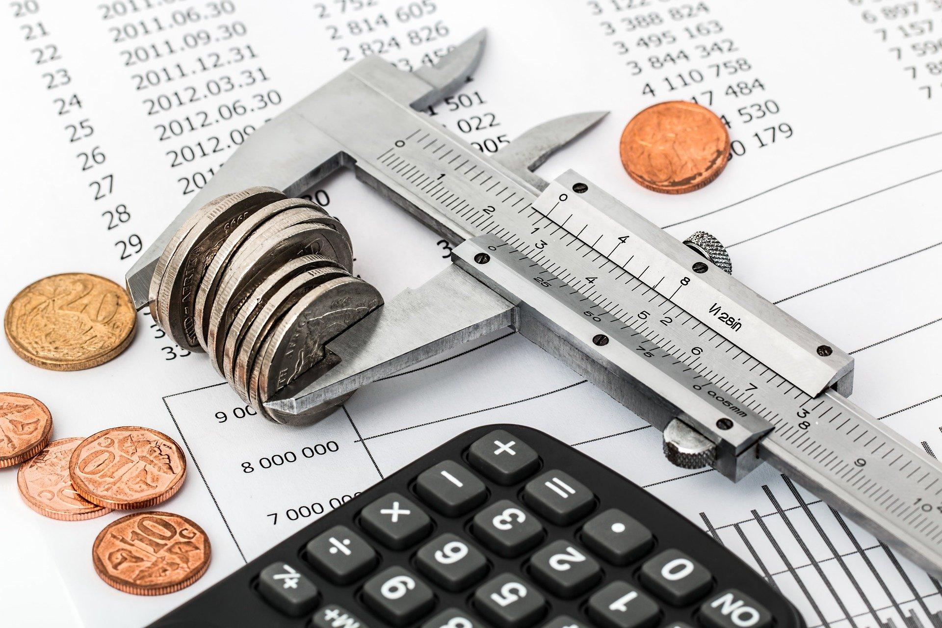 Imagem de um paquímetro medindo moedas. Imagem ilustrativa texto bons negócios para investir.