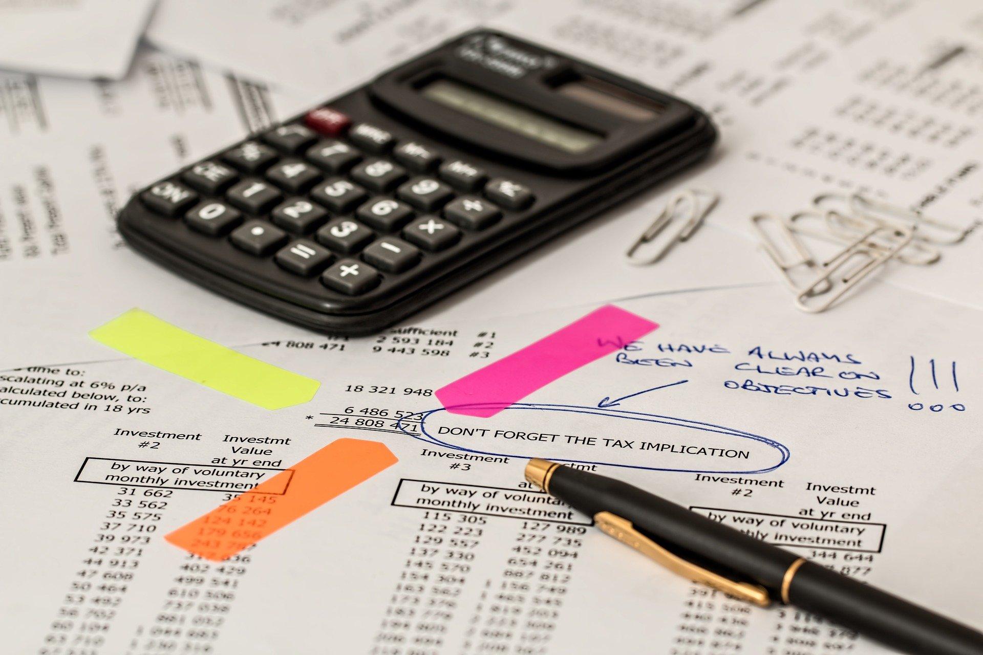 Imagem de uma calculadora e uma caneta em cima de papeis. Imagem ilustrativa texto como abrir uma mei.