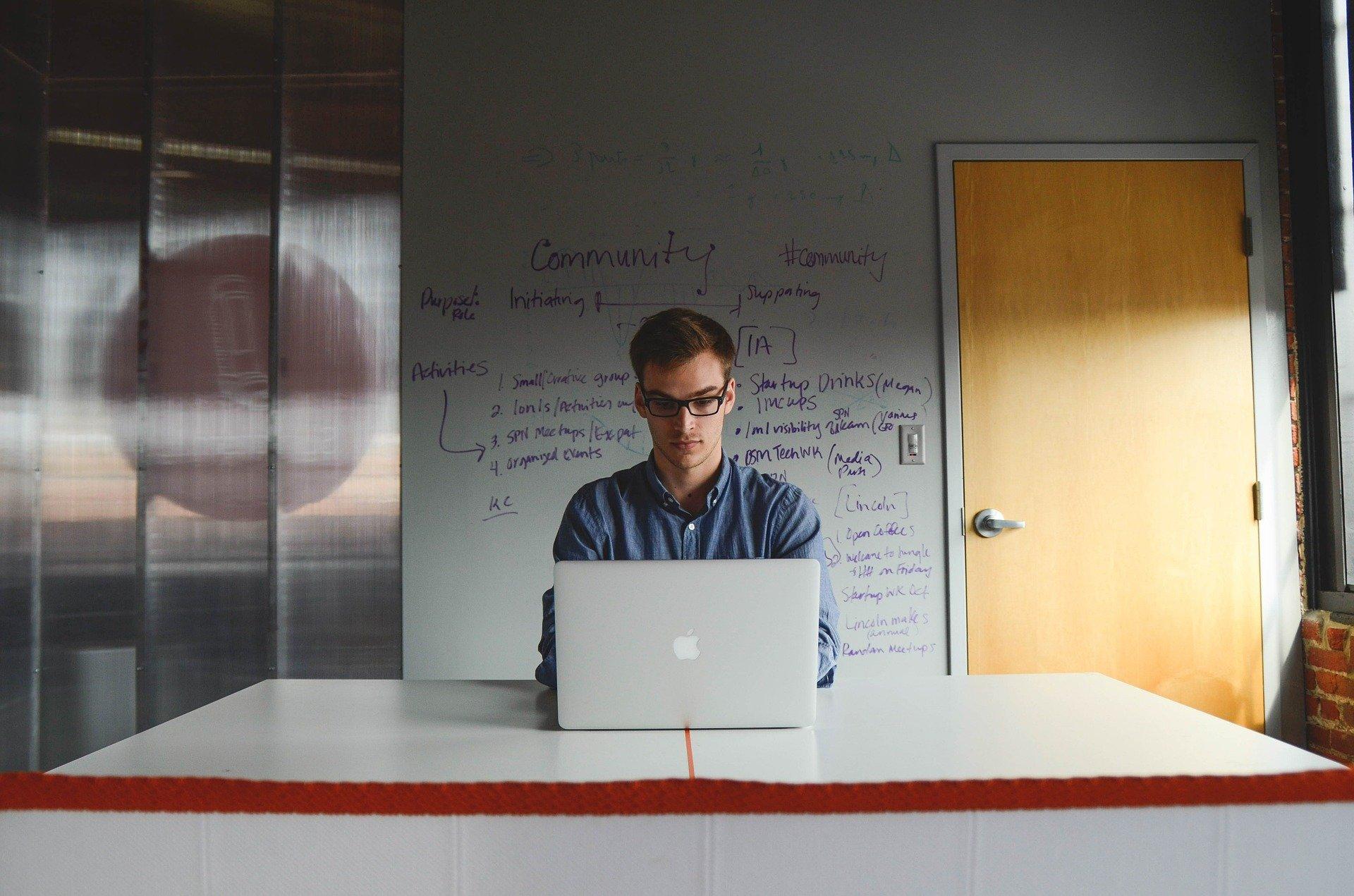 Imagem de um jovem em frente um computador trabalhando, com textos sobre negócios na parede atrás dele. Imagem ilustrativa texto como empreender sendo jovem.