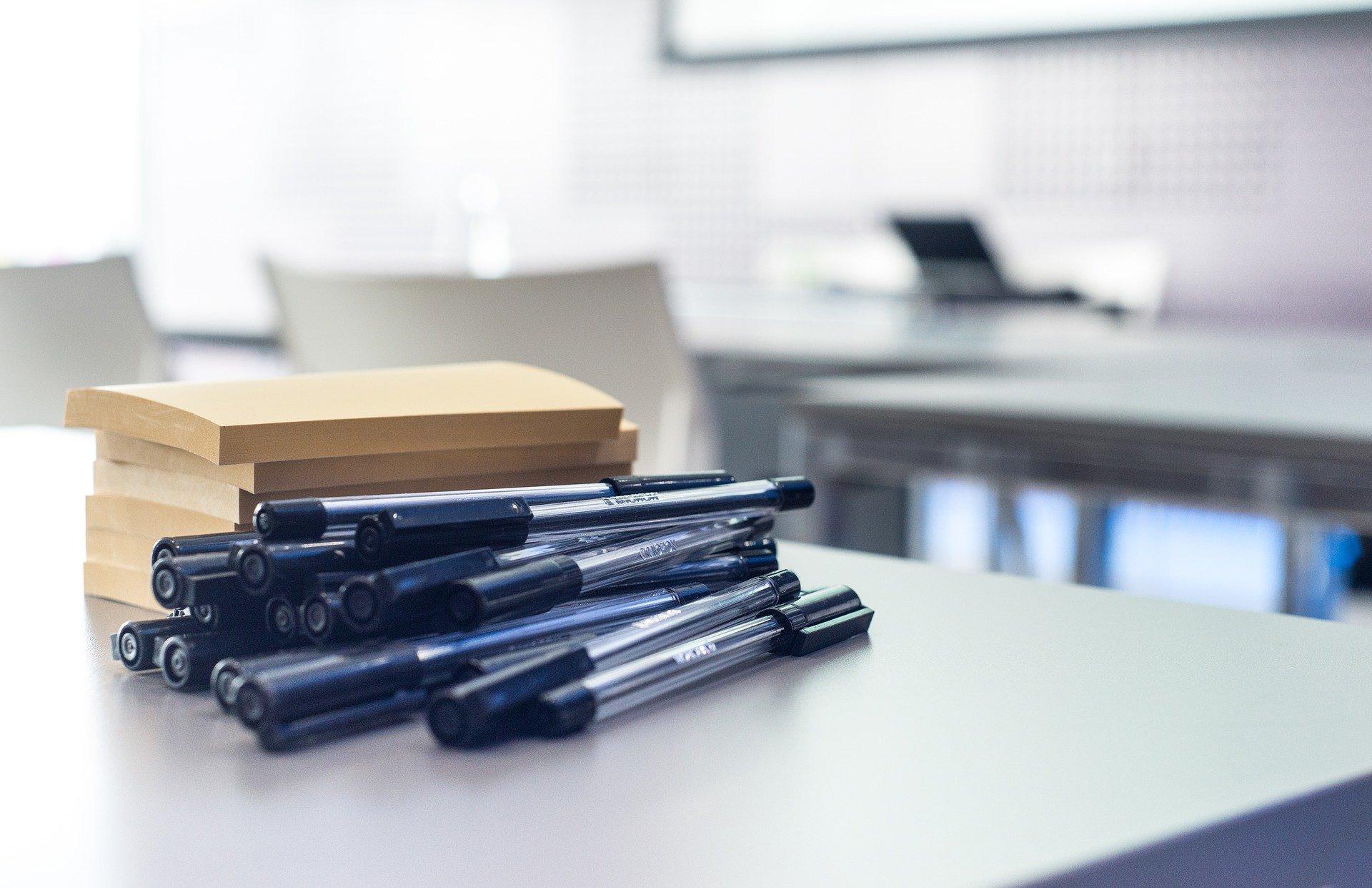 Vemos várias canetas ao lado de blocos de anotação sobre uma mesa (imagem ilustrativa). Texto: como montar uma empresa.