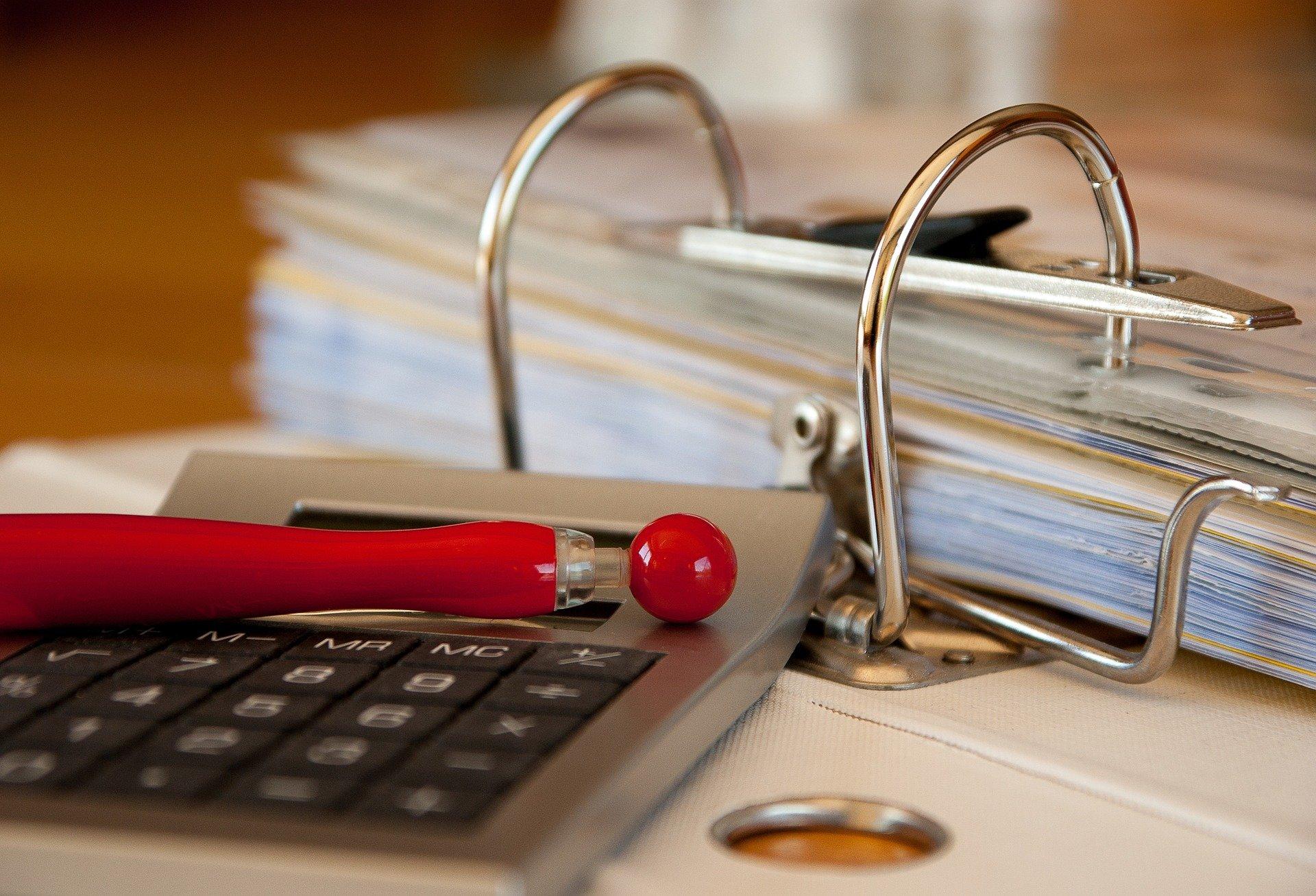 Vemos uma calculadora e um bloco de arquivar papel sobre uma mesa (imagem ilustrativa). Texto: como montar uma empresa.