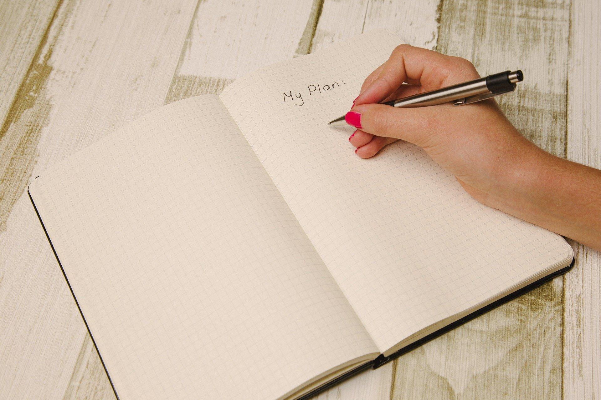 Imagem de uma mão escrevendo PLAN em um caderno. Imagem ilustrativa texto como montar uma empresa.