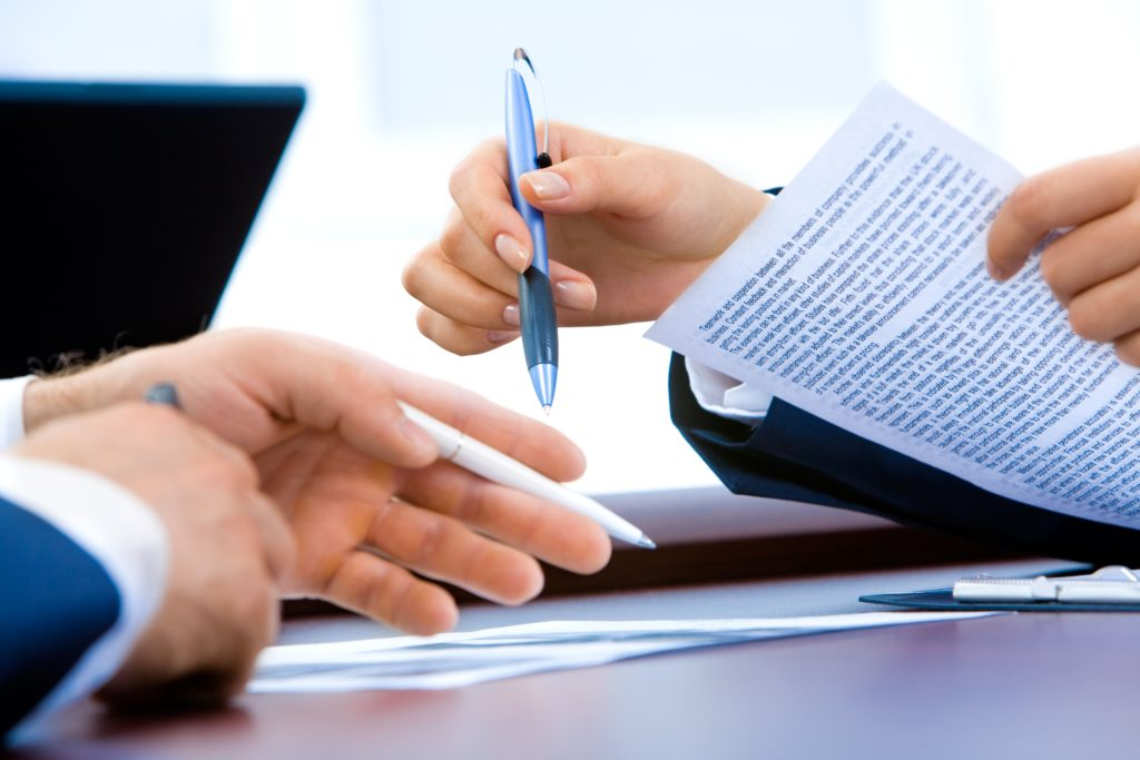 Vemos que uma empresária e um empresário, ambos segurando uma caneta, discutem a respeito de um documento (imagem ilustrativa). Texto: custos franquia.