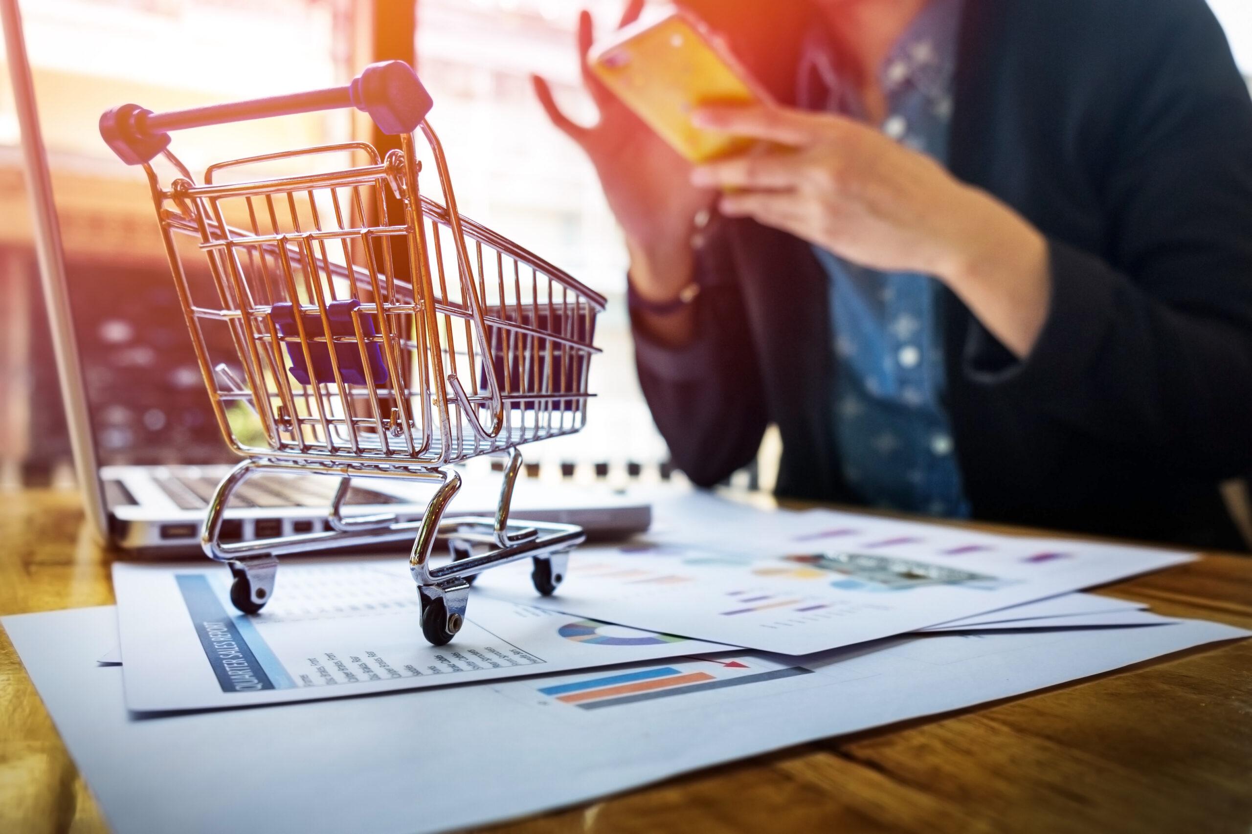 Imagem de um carrinho de compras e de uma pessoa usando um telefone. Imagem ilustrativa texto e-commerce.
