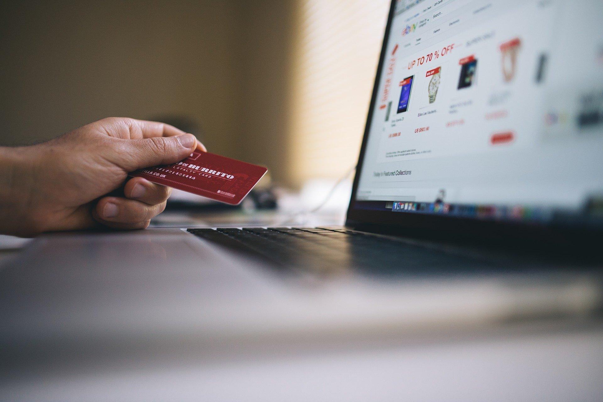 Vemos uma pessoa segurando um cartão de crédito perto de um computador (imagem ilustrativa). Texto: e-commerce.