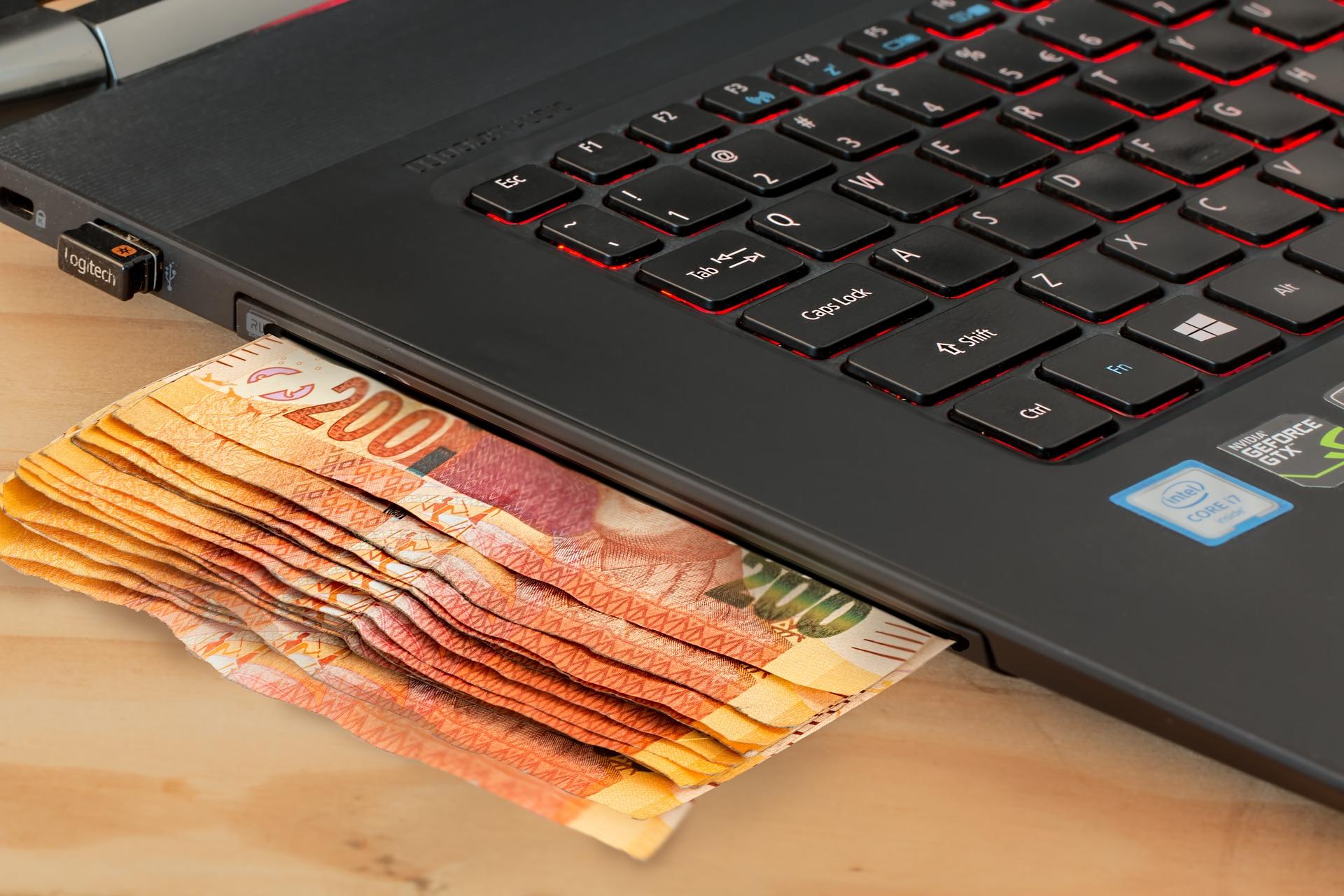 Vemos algumas notas de dinheiro ao lado de um computador (imagem ilustrativa). Texto: e-commerce.