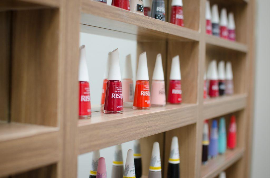 Vemos alguns esmaltes em uma prateleira (imagem ilustrativa). Texto: fidelizar clientes no mercado de beleza.