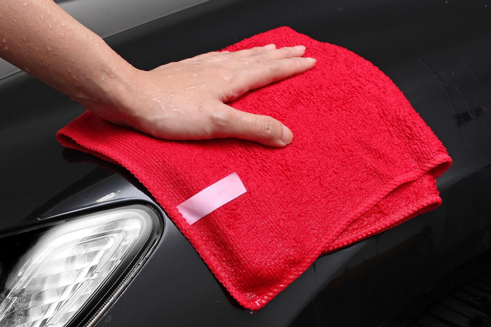 Vemos que uma pessoa utiliza uma flanela vermelha para limpar o capô de um carro (imagem ilustrativa). Texto: franquia zaplus car.