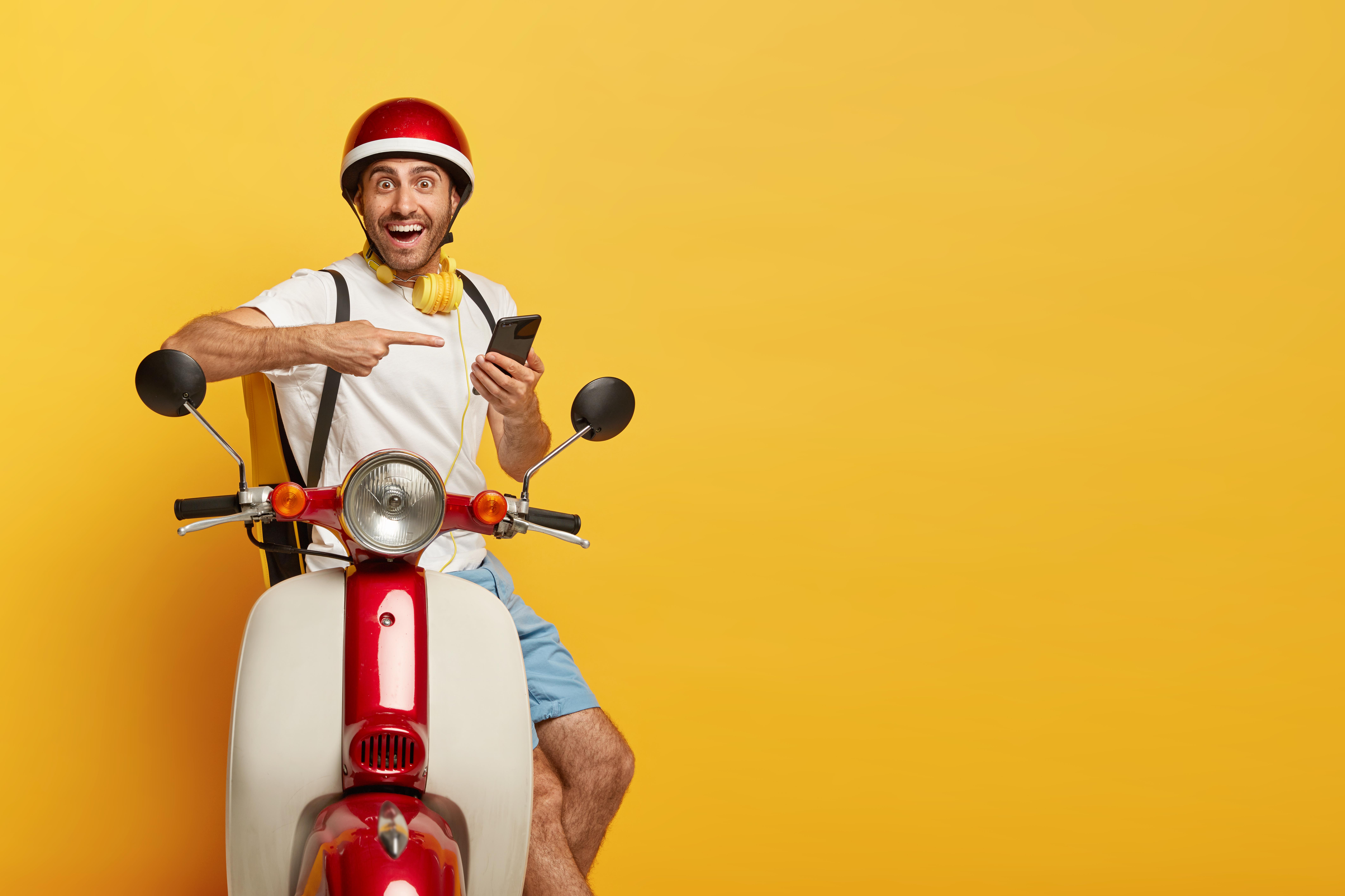 Vemos um motoboy com um celular na mão enquanto aponta seu indicador direito para o dispositivo com um semblante sorridente (imagem ilustrativa). Texto: franquias ideias para quem tem até 35 anos.