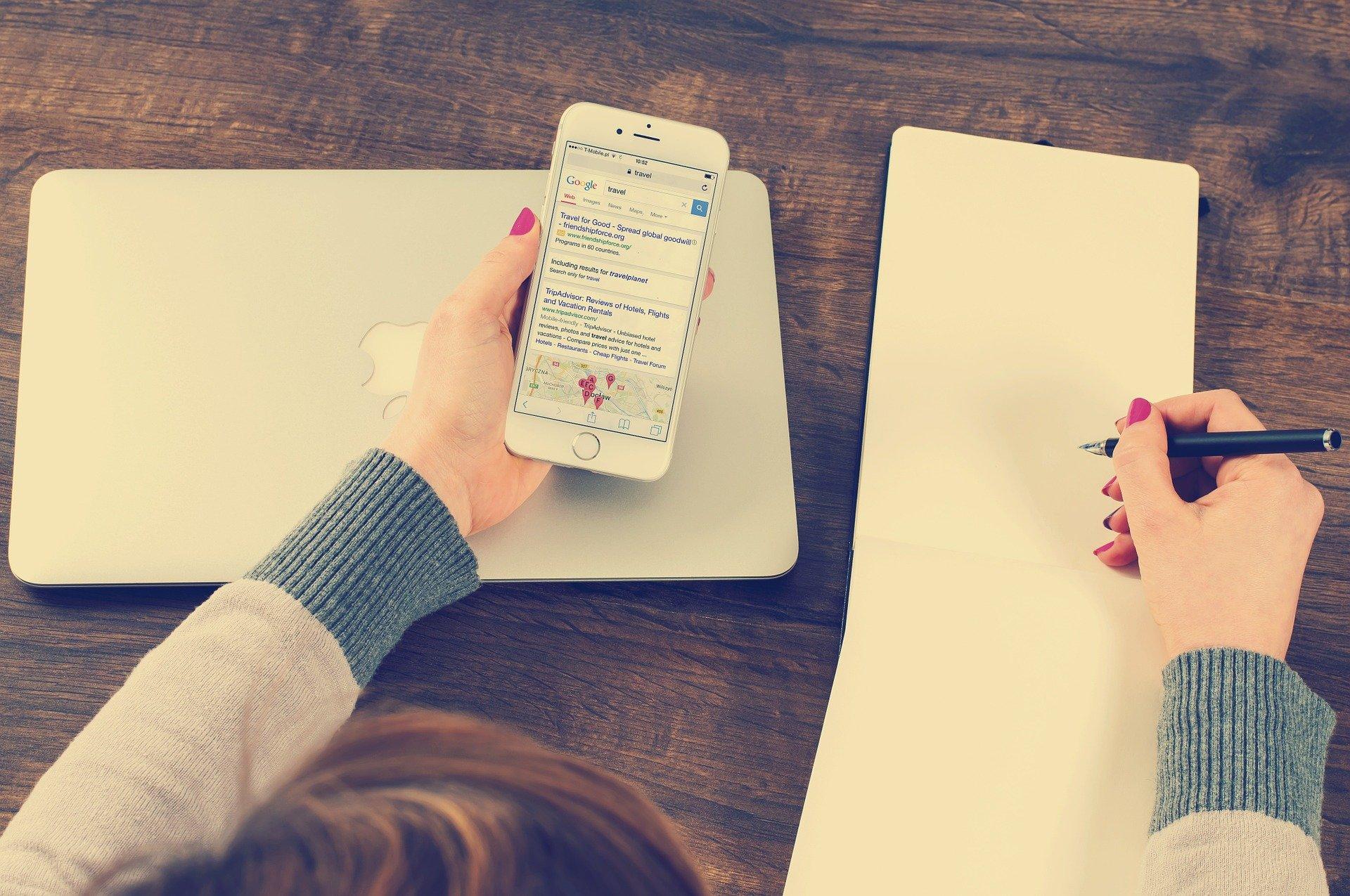 Vemos uma mulher segurando um celular e escrevendo algo em uma folha (imagem ilustrativa).