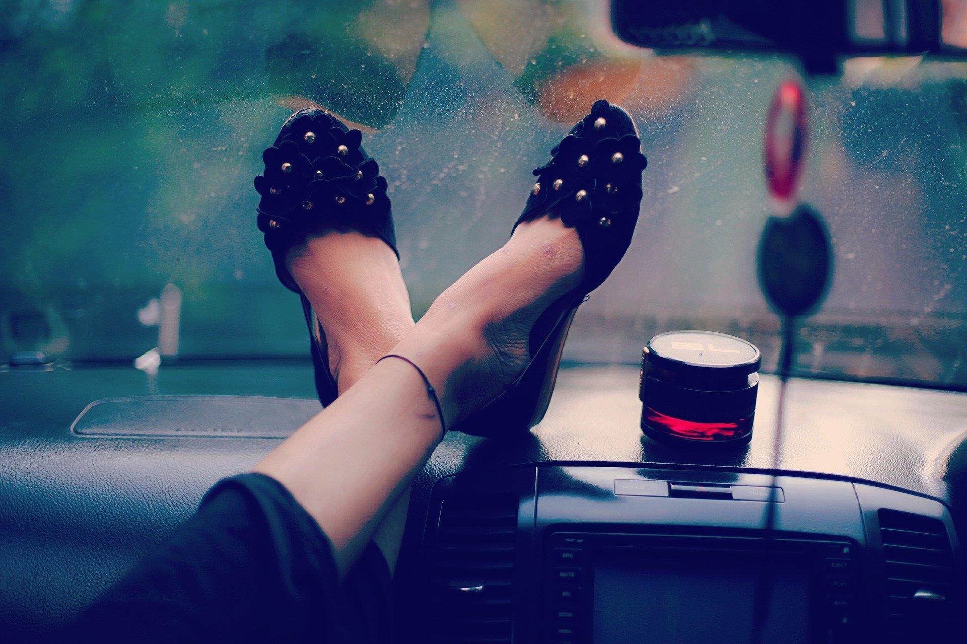 Vemos pés femininos sobre o painel de um carro (imagem ilustrativa). Texto: ideias de negócios lucrativos.