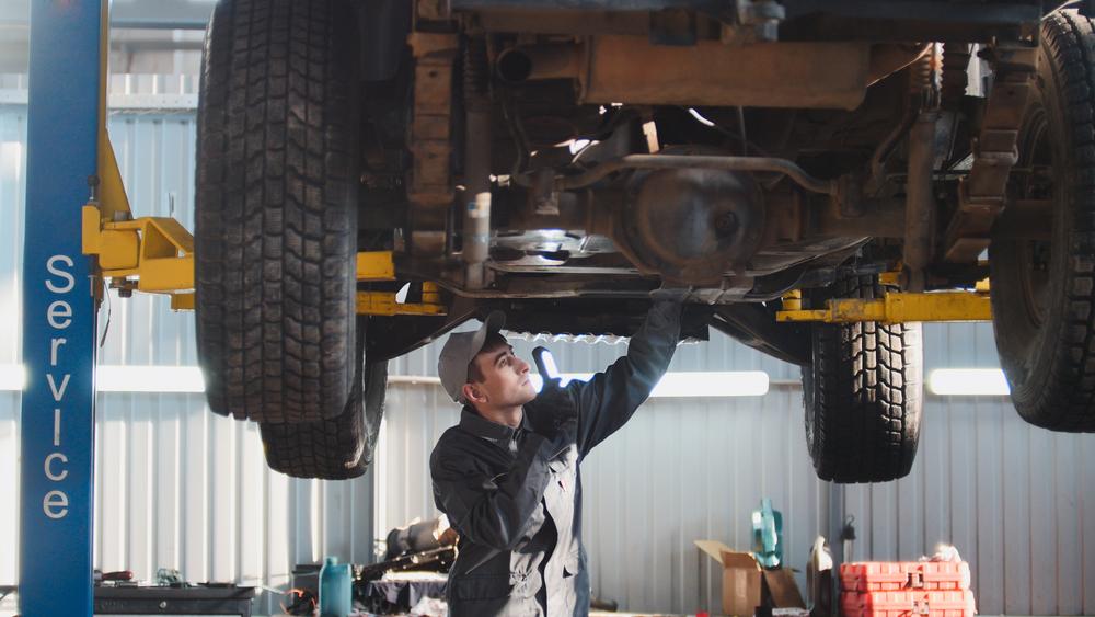 Vemos um mecânico analisando a parte inferir de um carro suspenso (imagem ilustrativa). Texto: investir em uma franquia automotiva.