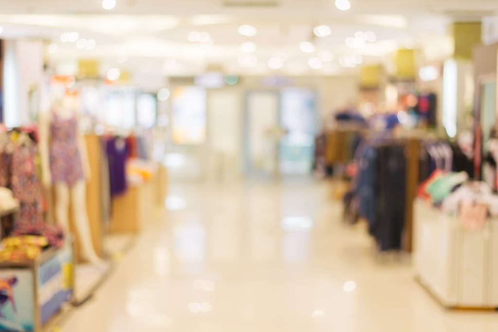 Vemos um grande corredor de loja de roupa em uma imagem desfocada.