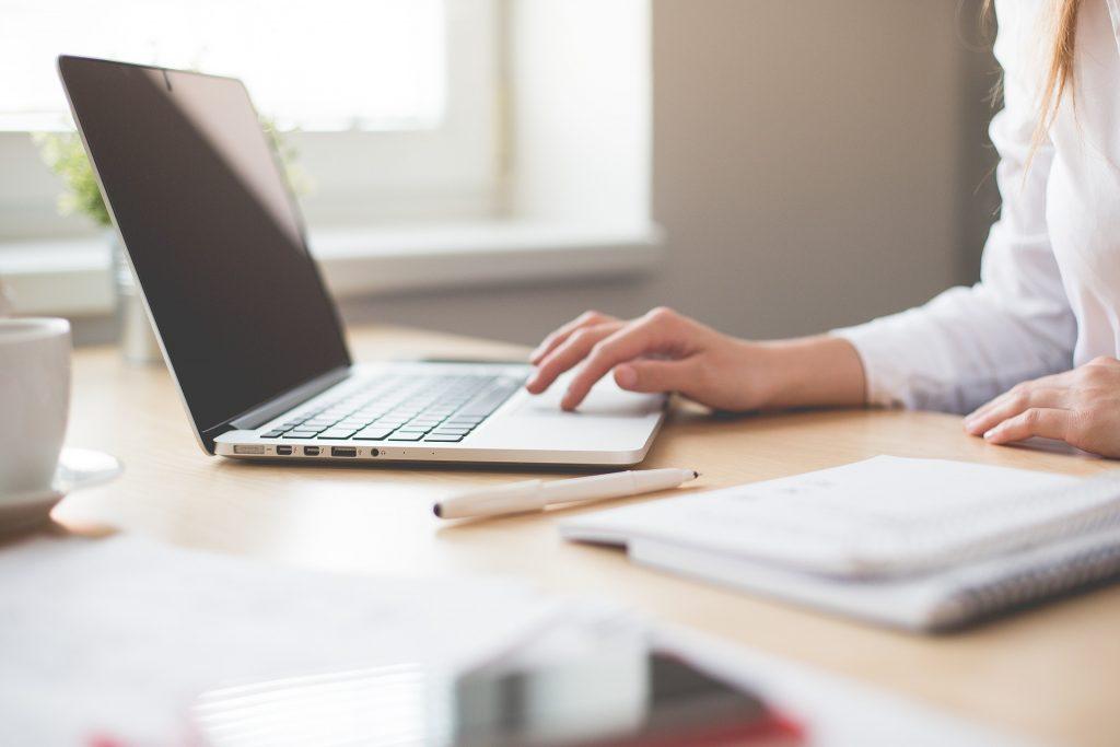 Vemos uma mulher trabalhando em seu home office. Sobre a mesa temos uma xícara de café, um computador, caneta e dois cadernos de anotação (imagem ilustrativa). Texto: loja ou quiosque.