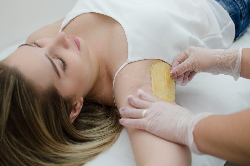 Vemos que uma mulher está realizando o procedimento de depilação nas axilas (imagem ilustrativa). Texto: mercado de beleza.
