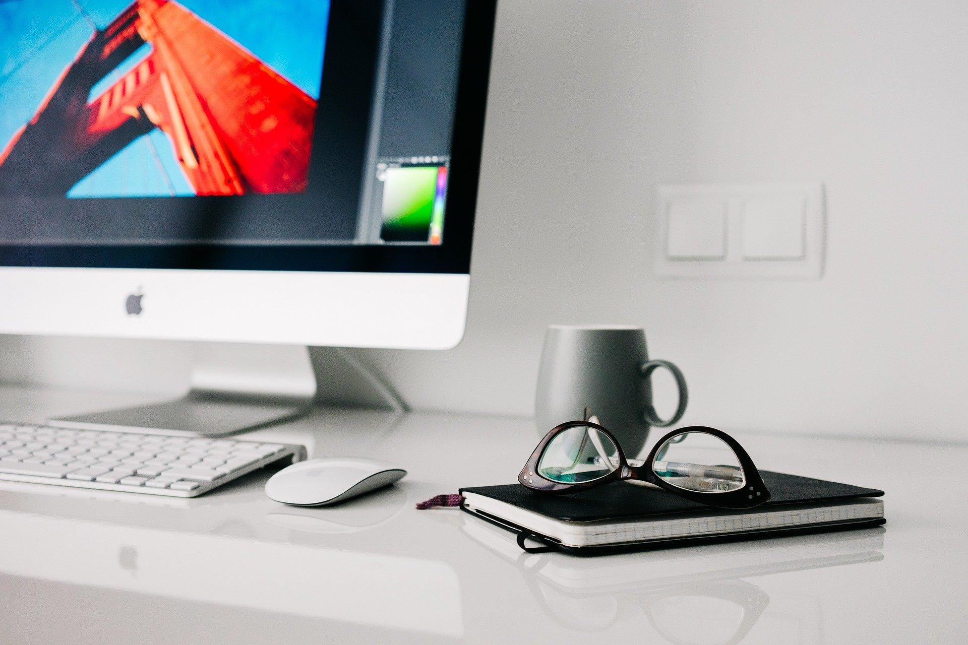 Vemos a mesa do escritório de uma pessoa; há um computador, agenda, óculos e uma xícara de café (imagem ilustrativa). Texto: negócios para abrir em casa.