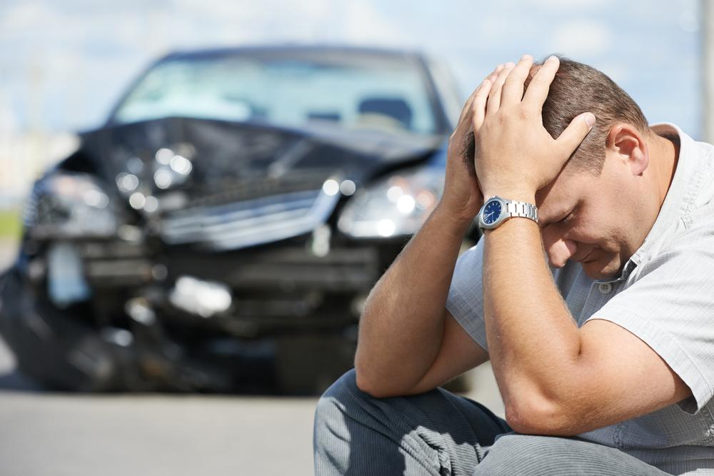 Vemos um homem sentado com as mãos na cabeça. Seu semblante é de preocupação, pois, ao fundo, vemos que ele acaba de bater com o seu carro (imagem ilustrativa). Texto: seguro de carro.