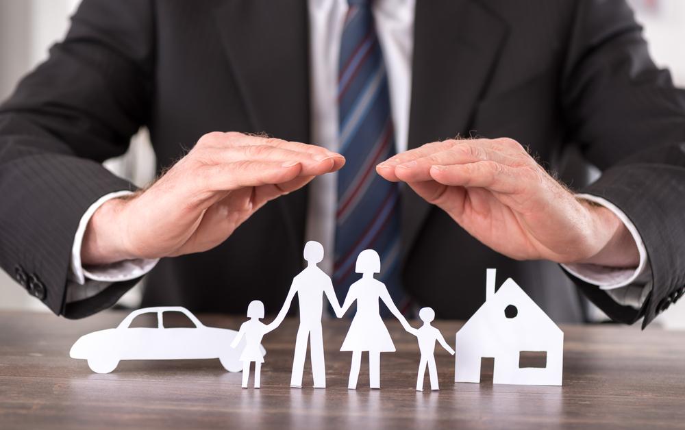 """Vemos que um corretor se seguro faz uma """"proteção"""" com as mãos em cima da representação de uma família com pai, mãe, filhos, uma casa e um caro, feita a partir de um recorte de papel (imagem ilustrativa)."""