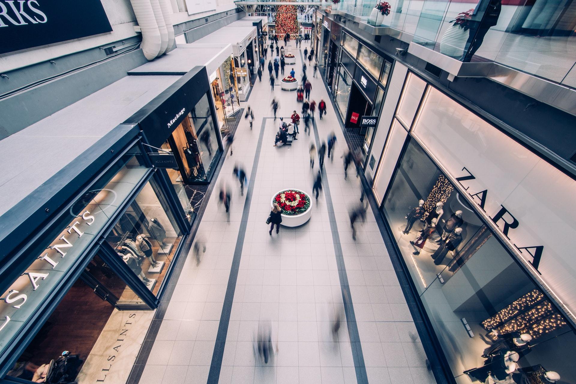 Vemos um corredor de um shopping com pessoas andando (imagem ilustrativa).