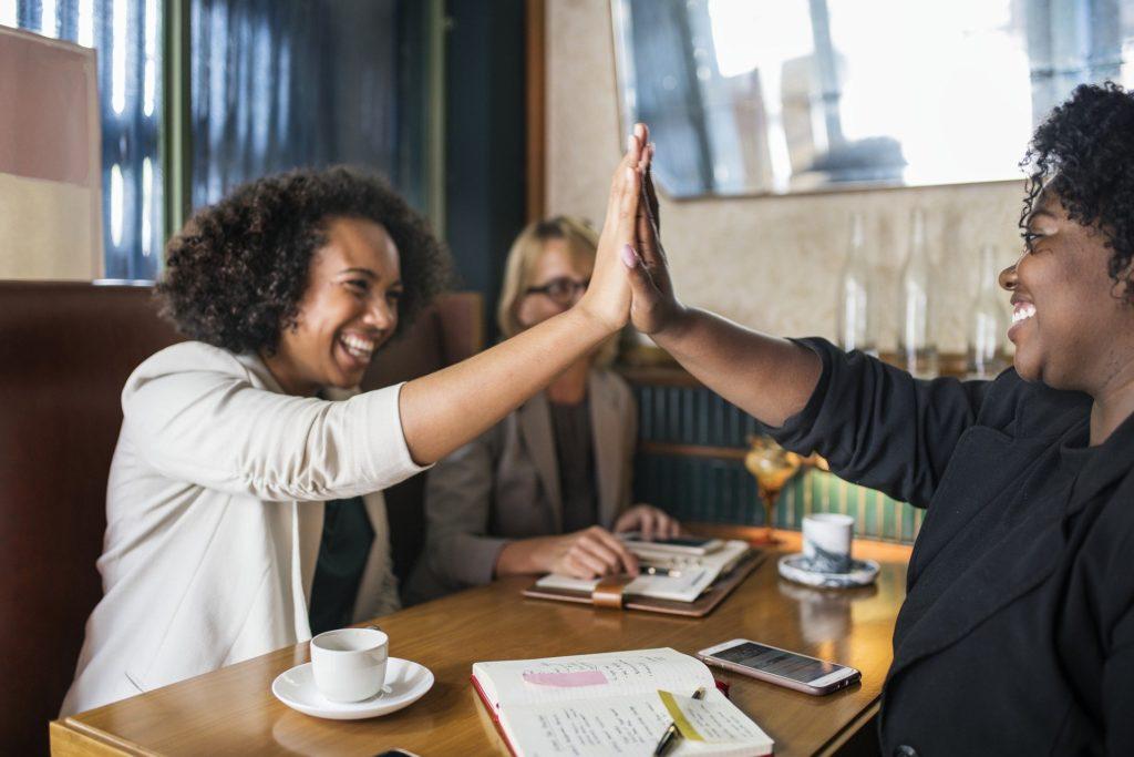 Vemos três mulheres realizando uma reunião em uma cafeteria; as três, com sorriso no rosto, parecem ter tido uma reunião produtiva (imagem ilustrativa). Texto: cansado do emprego.