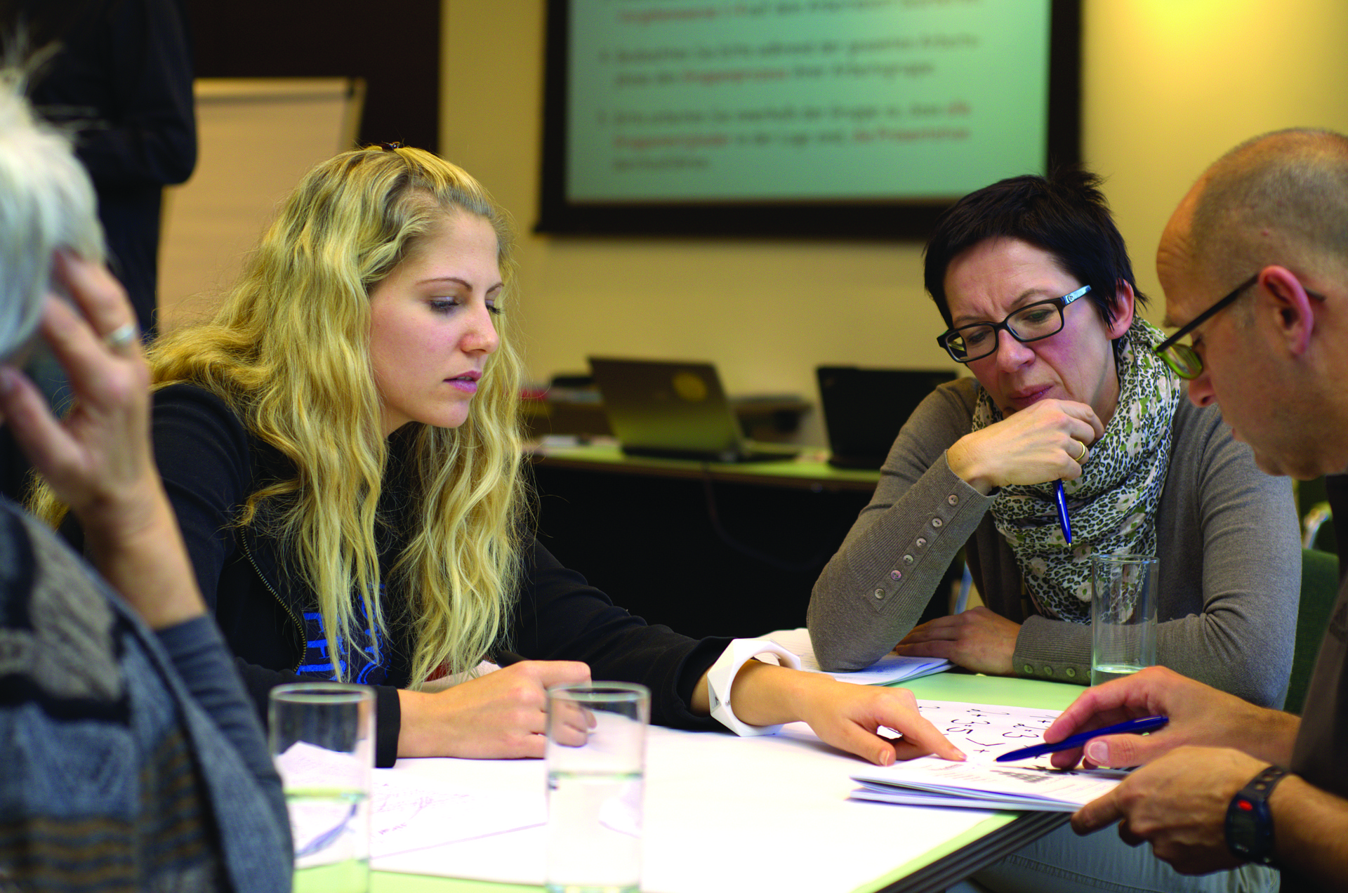 Vemos três mulheres conversando com um homem em uma espécie de reunião (imagem ilustrativa). Texto: como abrir uma franquia de açaí.