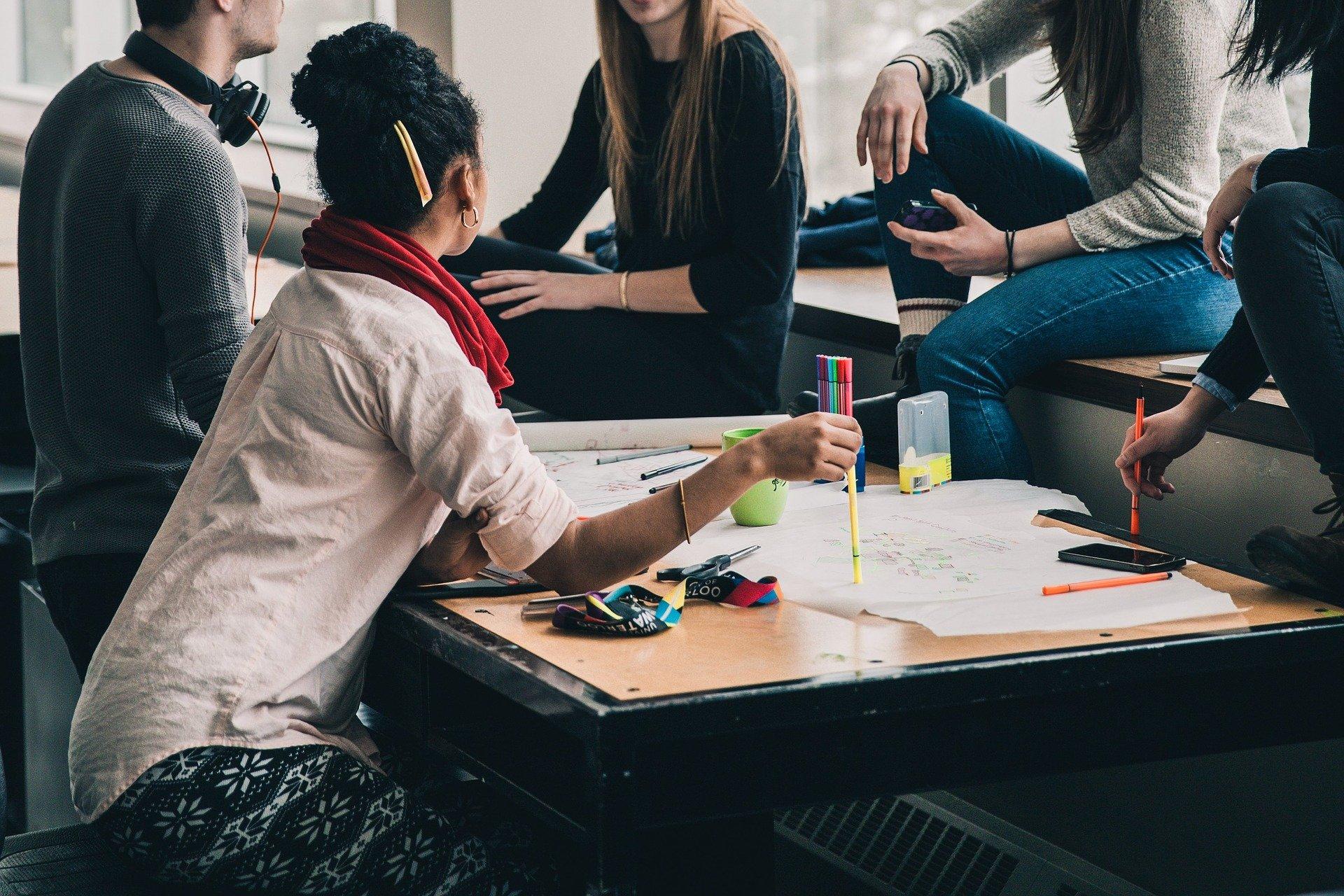 Vemos algumas pessoas conversando ao redor de uma mesa (imagem ilustrativa). Texto: como abrir uma franquia de açaí.