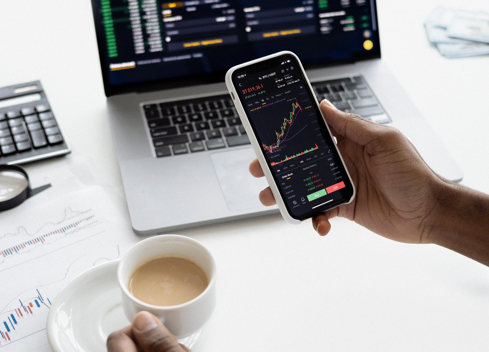 Vemos que uma pessoa segura um telefone com gráficos na tela, acompanhado de um computador que acompanha as movimentações do mercado financeiro (imagem ilustrativa). Texto: como franquear minha marca.