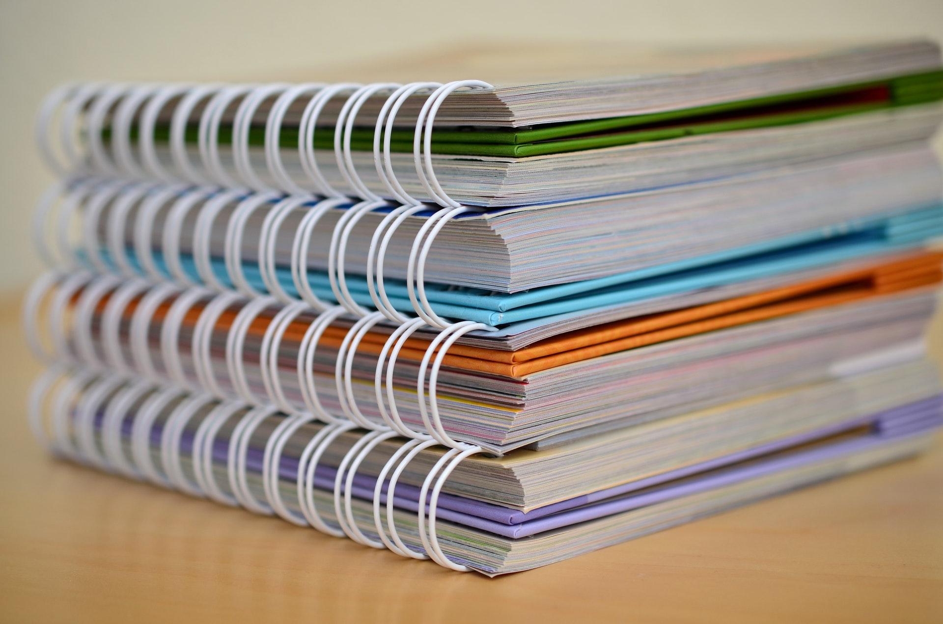 Vemos vários cadernos empilhados (imagem ilustrativa). Texto: como franquear minha marca.