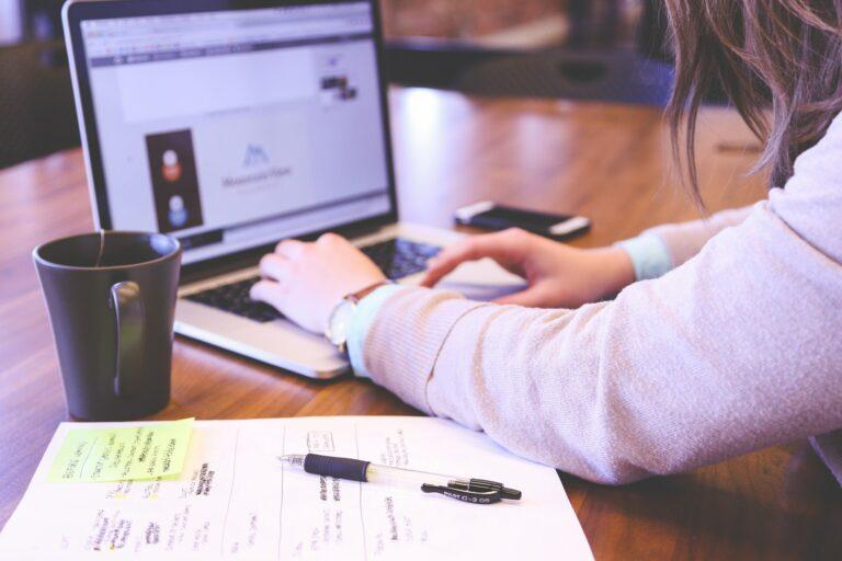 Imagem de uma pessoa mexendo no computador em uma mesa de escritório. Imagem ilustrativa texto como franquear minha marca.