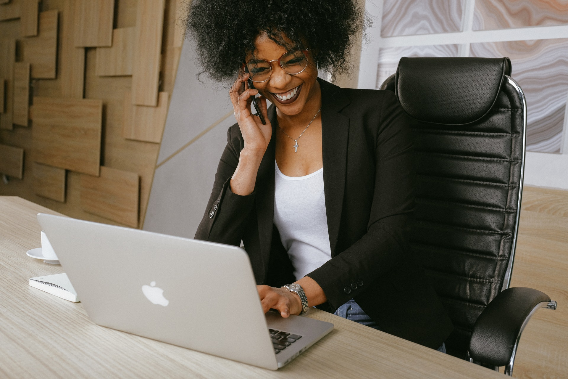 Imagem de uma empresária ao telefone e usando um computador. Imagem ilustrativa texto empreendedor individual.
